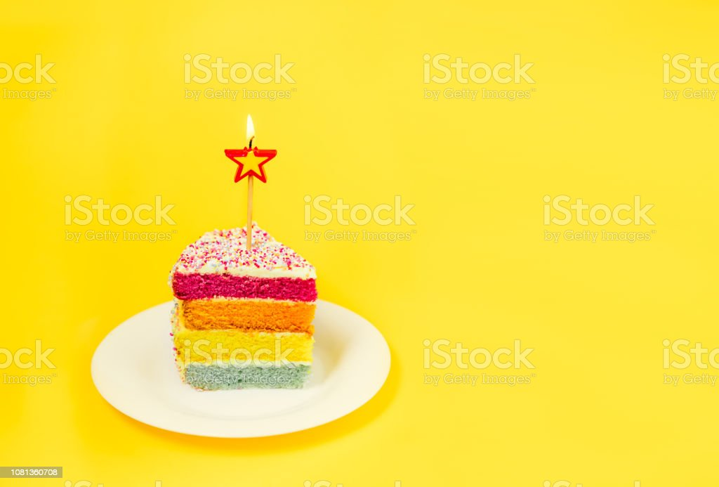 Slice of Rainbow cake with birning candle in the shape of star on white round plate isolated on bright yellow background. Happy bithday, party concept. Selective focus. Copy space. stock photo