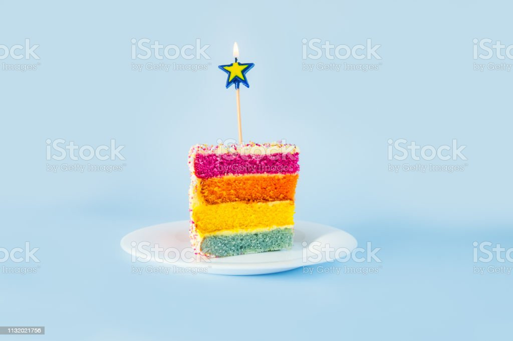 Slice of Rainbow cake with birning candle in the shape of star on white round plate isolated on blue background. Happy bithday, party concept. Selective focus. Copy space. stock photo