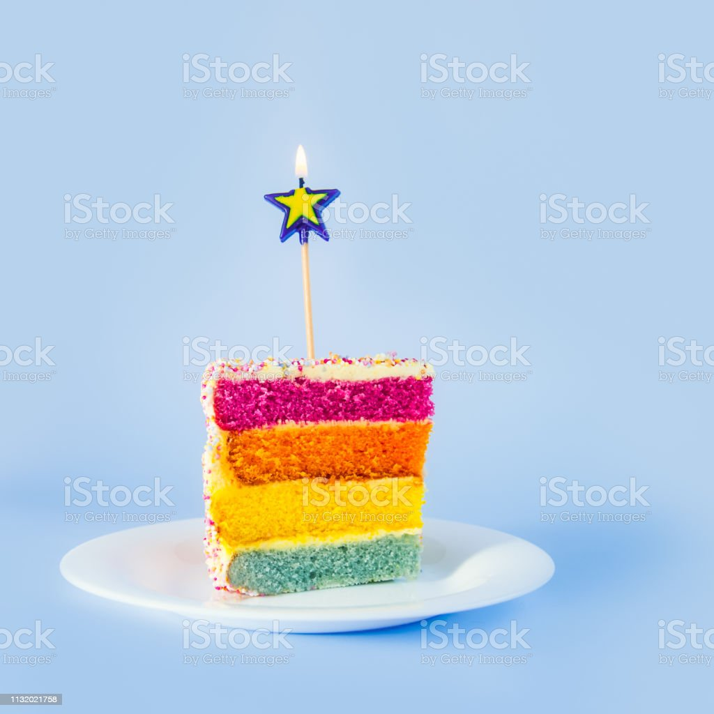 Slice of Rainbow cake with birning candle in the shape of star on white round plate isolated on blue background. Happy bithday, party concept. Square card. Selective focus. Copy space. stock photo