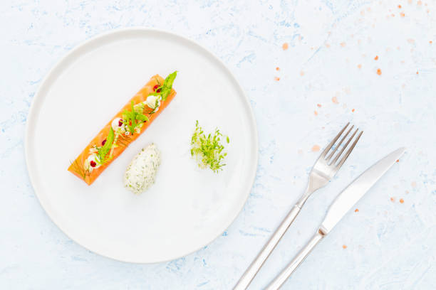 Slice of raw salmon with asparagus, edamame, beetroot, cream cheese and bean sprout, dill and cream cheese quenelle on a blue background with cutlery. Flat lay. stock photo