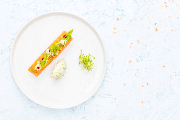 Slice of raw salmon with asparagus, edamame, beetroot, cream cheese and bean sprout, dill and cream cheese quenelle on a blue background. Flat lay. stock photo