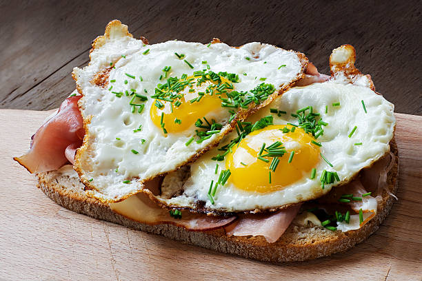 slice of rustic bread with ham  and fried eggs - fried egg stock photos and pictures