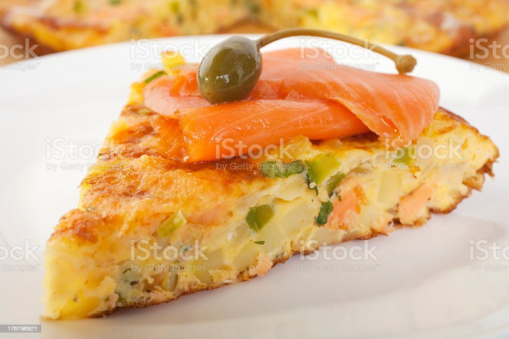 Slice of salmon frittata with caperberry on a white plate stock photo