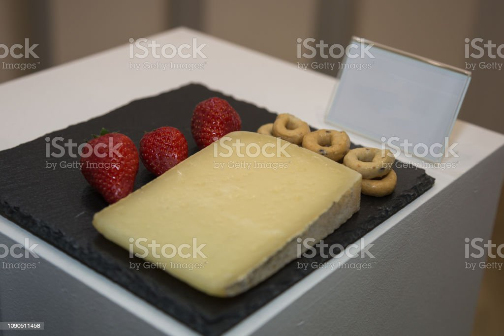 Slice of Sheep's Cheese on Black Tablecloth decorated with Italian Taralli and Strawberries stock photo