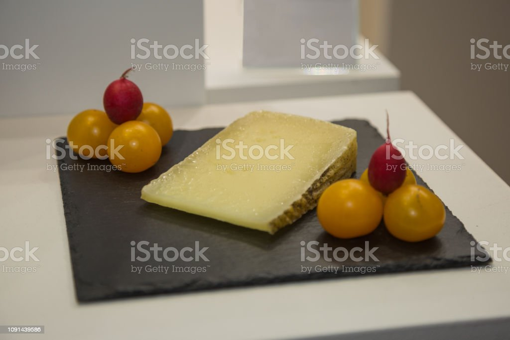 Slice of Sheep's Cheese on Black Tablecloth with Yellow Tomatoes and Red BeetRoots stock photo