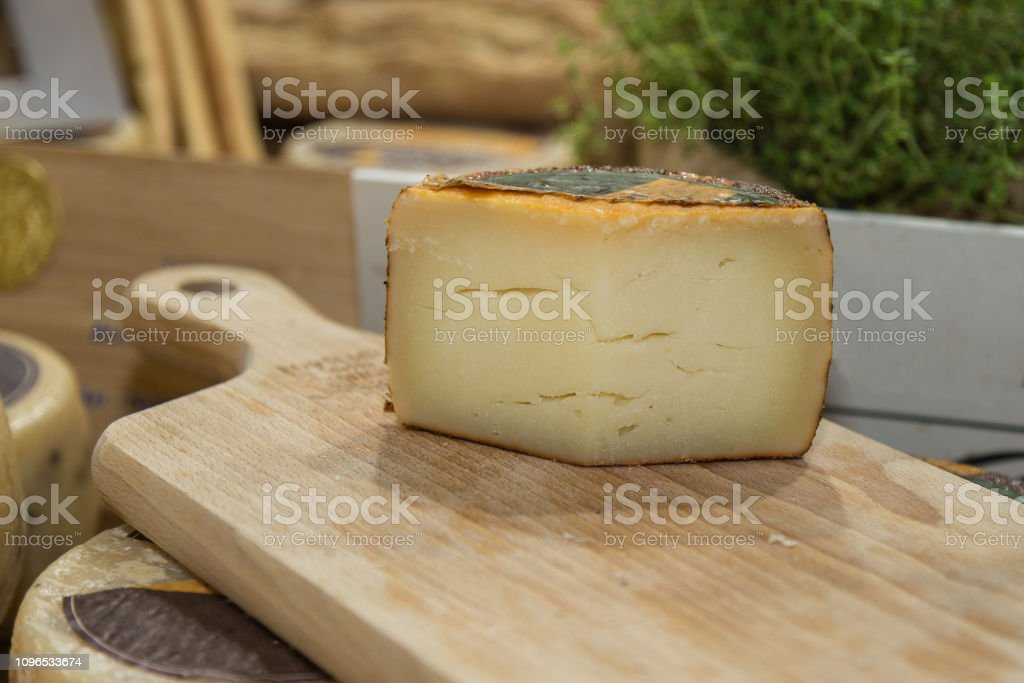 Slice of Sheep's Cheese Resting on a Wooden Chopping Board stock photo