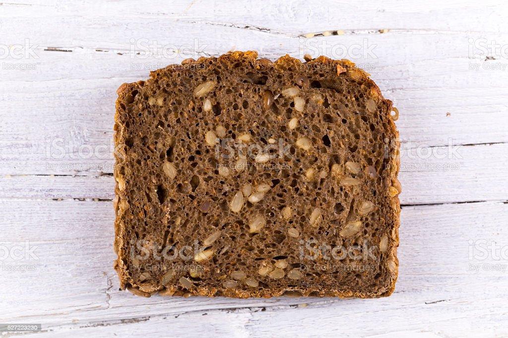 slice of sunflower bread on white wooden background stock photo
