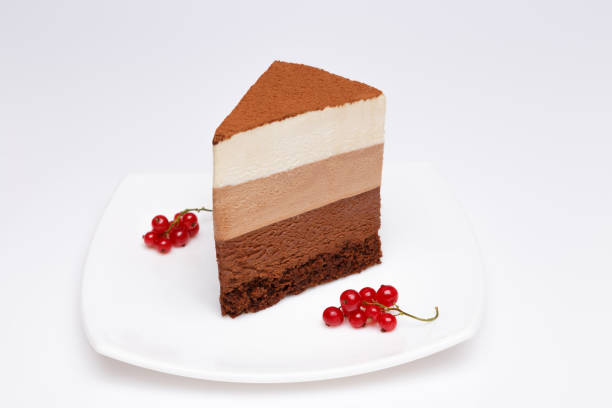 slice of the three chocolate mousse cake on a white plate stock photo