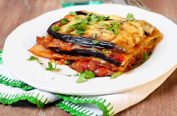 Slice of vegetable lasagna on a white plate on wooden table stock photo