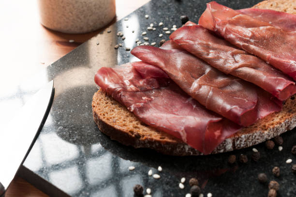 slice of wholemeal bread with bresaola (dried beef) on a black granite cutting board. - bresaola foto e immagini stock