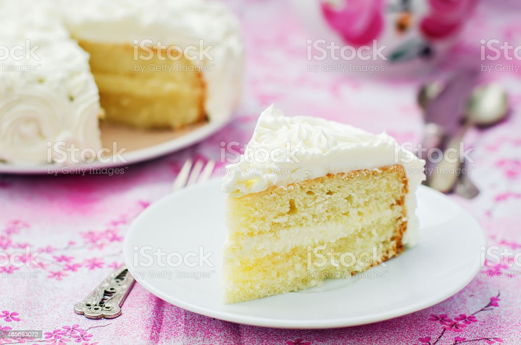 Slice of yellow cake with white frosting on pink table stock photo