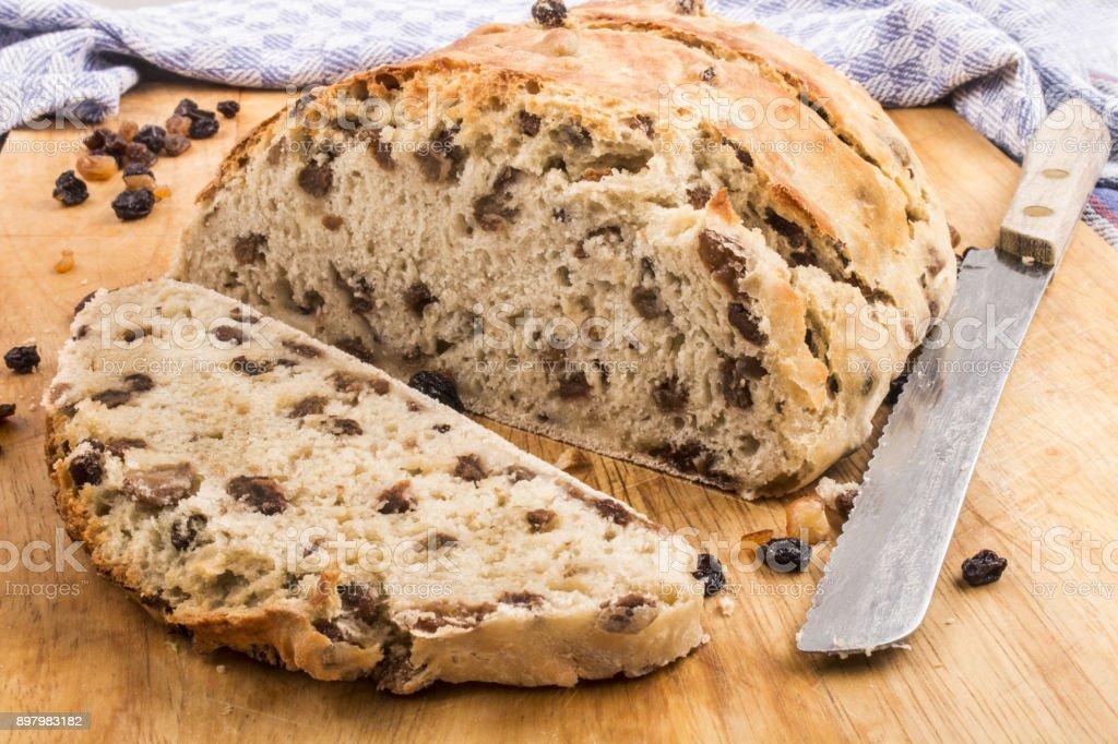 slice raisin bread with bread knife on a wooden board stock photo