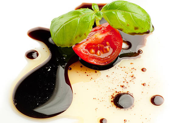 slice tomato and basil slice tomato and basil  over olive oil and balsamic vinegar on white background balsamic vinegar stock pictures, royalty-free photos & images