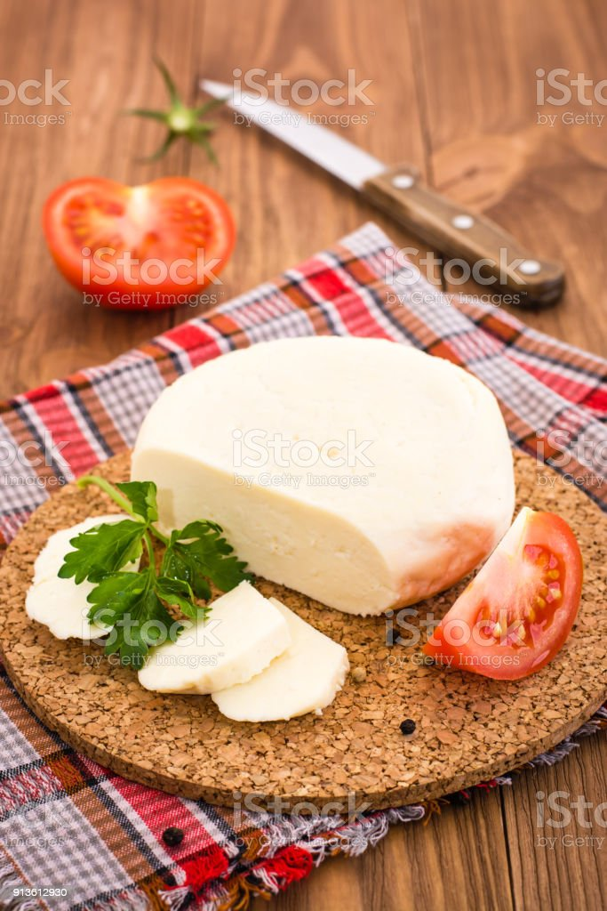 Sliced Adyghe cheese, tomato and parsley on a substrate stock photo