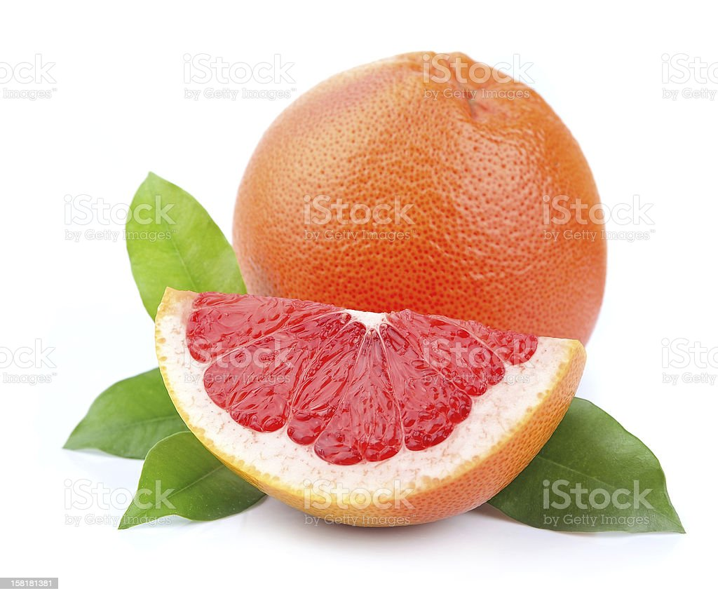 Sliced and whole grapefruit with leaves against white stock photo