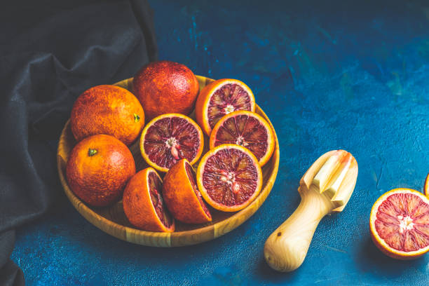 Sliced and whole Sicilian Blood oranges fruits in wooden plate stock photo