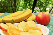 On the table in the garden are fruits. Sliced apples, bananas and apple. These fruits contain many vitamins. Healthly food.