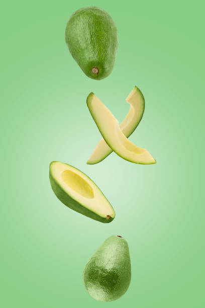 Sliced Avocado isolated in green surface viewed from above stock photo