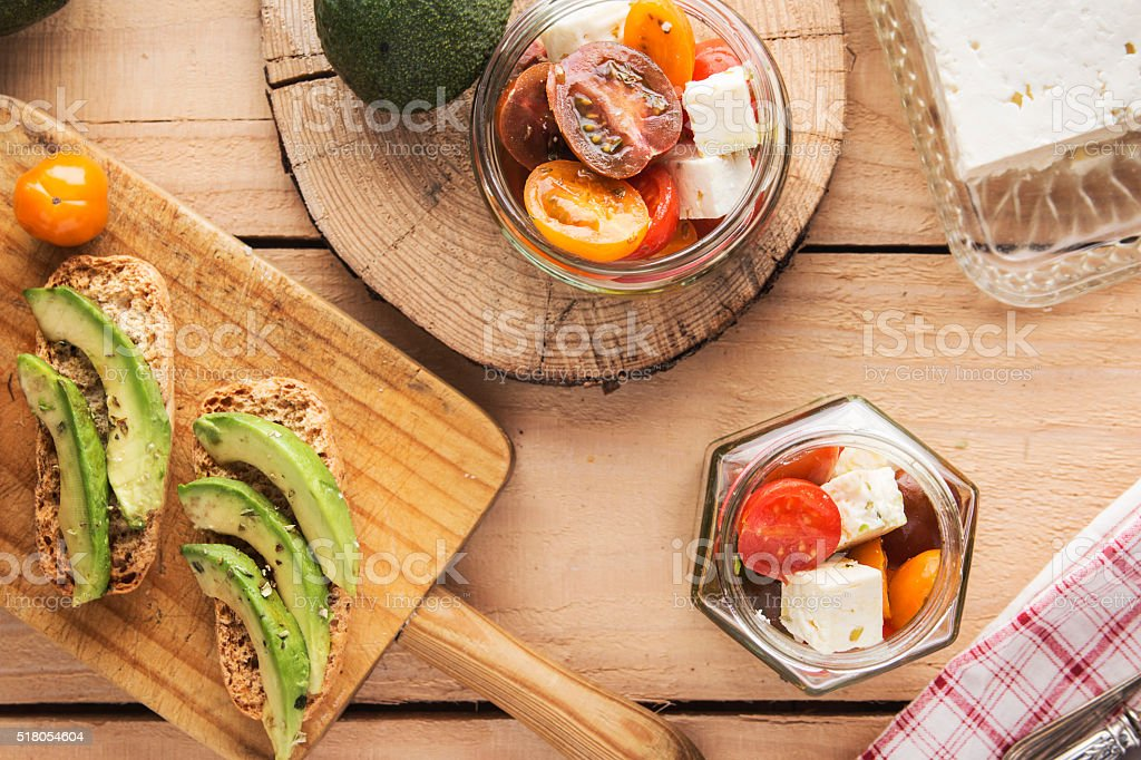 Sliced avocado on toast bread with spices and tomato salad stock photo