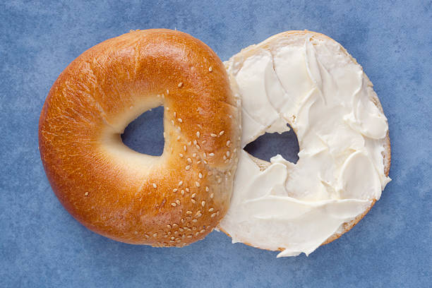 A sliced bagel spread with cream cheese stock photo