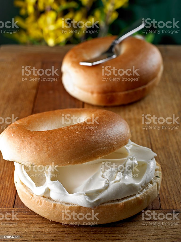 A sliced bagel with spread cheese in it stock photo