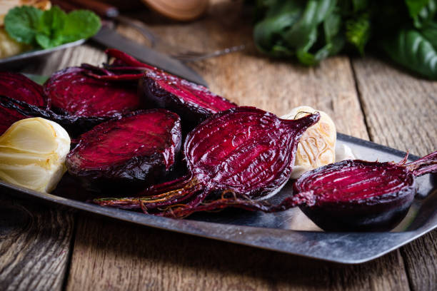 Sliced baked beetroot on rustic outdoor party table stock photo