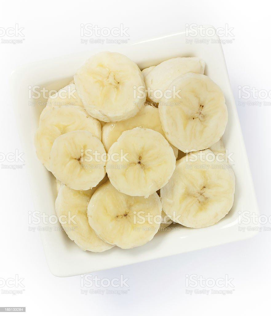 Sliced bananas in a square white bowl on a white background stock photo