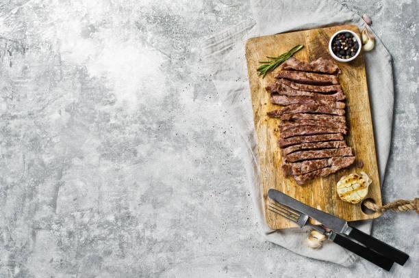 in scheiben geschnittenes rinderflanken-steak auf holzhoppe-board. grauer hintergrund, obere ansicht, platz für text - flank steak marinaden stock-fotos und bilder