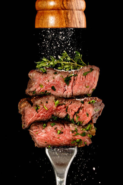 sliced beef steak from grill on a fork. salt is strewing from wooden mill - beef stock pictures, royalty-free photos & images