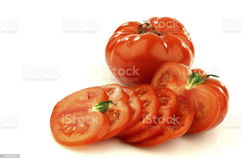 sliced beef tomato and a whole one stock photo