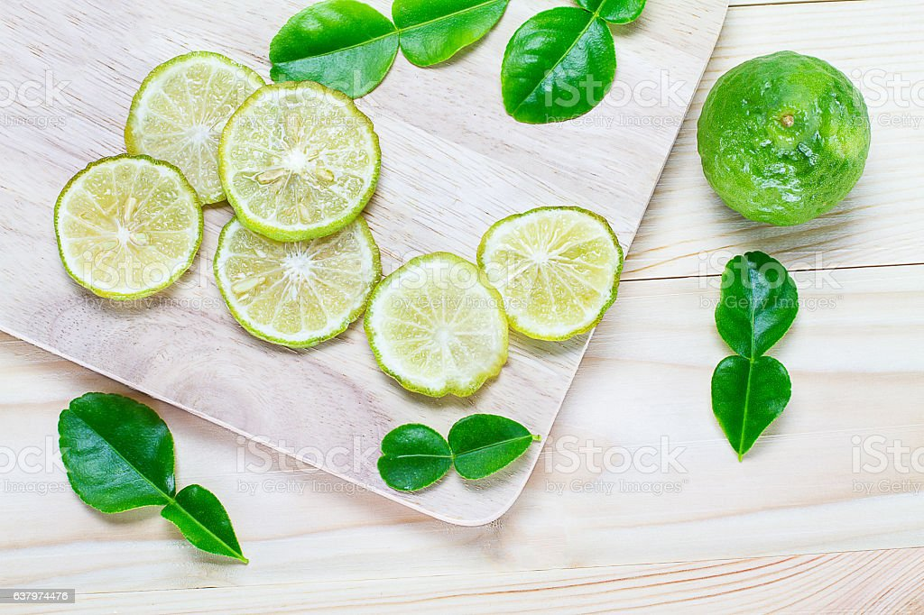 Sliced bergamot and leaves  on vintage wooden background stock photo