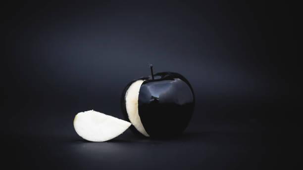 sliced black apple on a background stock photo