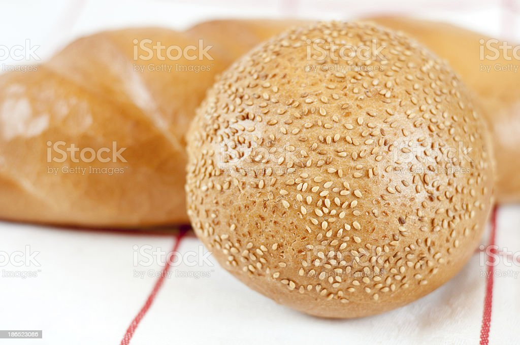 Sliced bread and bun with sesame seeds royalty-free stock photo