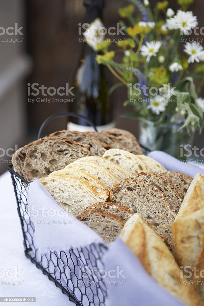 Sliced bread in basket with flowers in background, close-up royalty-free stock photo