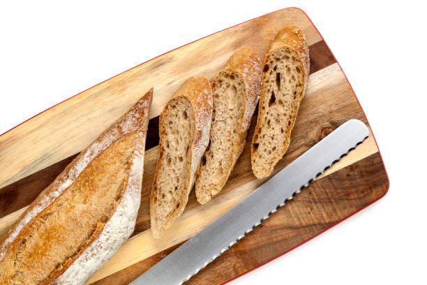 sliced bread stick on board top view - brotschneidebrett stock-fotos und bilder