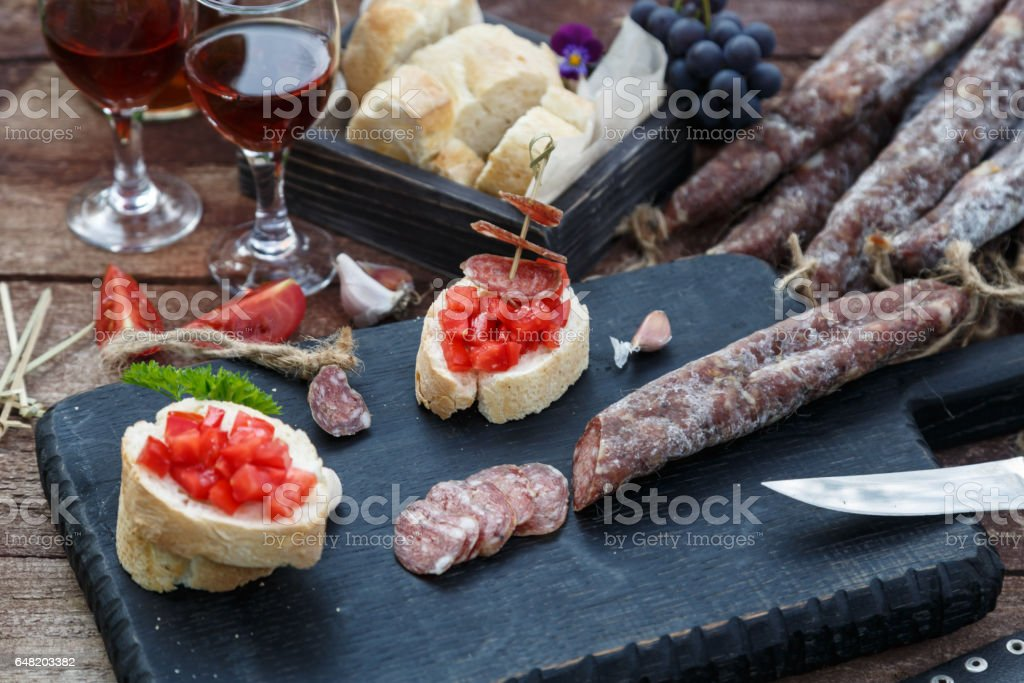 sliced bread, tomato and sausage for bruschettas on wooden cutting board stock photo