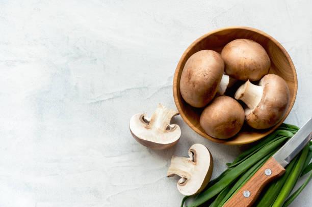 sliced brown champignons on concrete background. top view. - cogumelos imagens e fotografias de stock