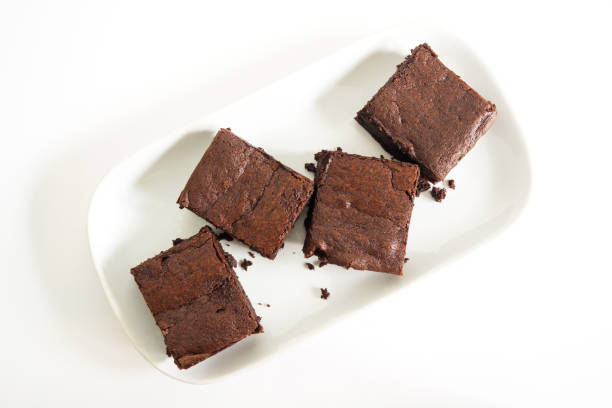 Sliced brownies on white plate. Served with chocolate fudge topping. On white plate with fork. - foto stock