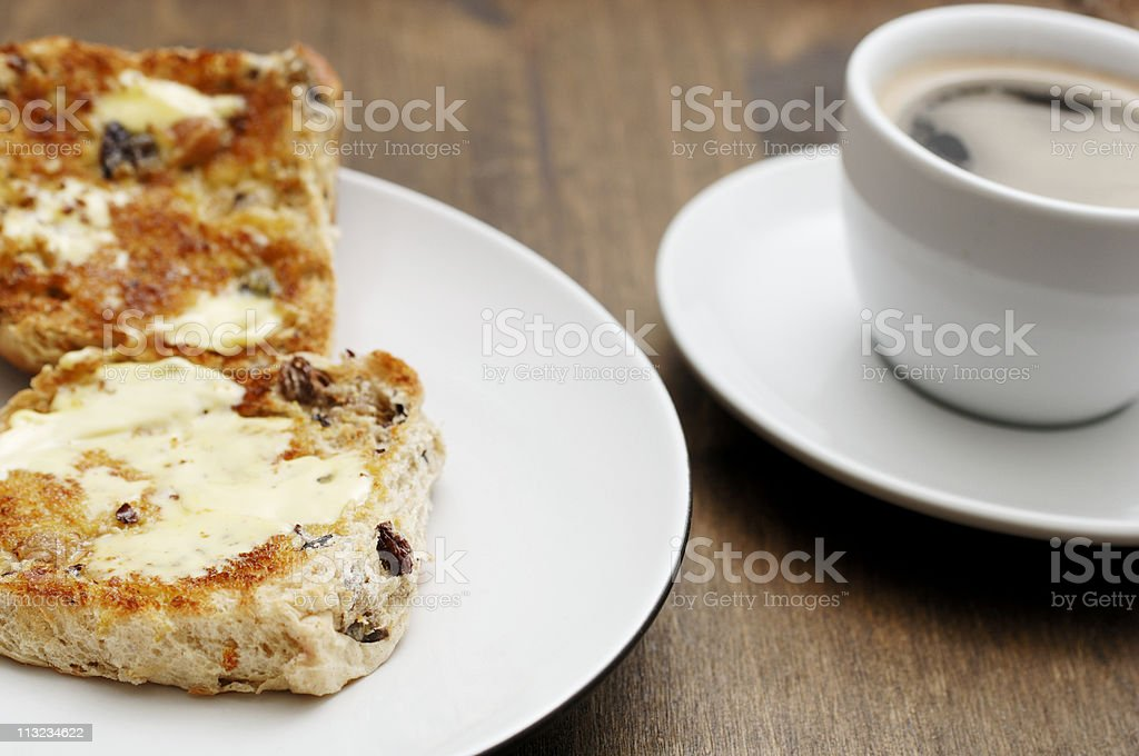 sliced, buttered hot cross bun with coffee royalty-free stock photo