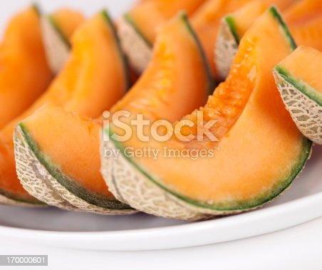 Portions of Cantaloupe on plate. Isolated on white background. Selective focus, shalow DOF.