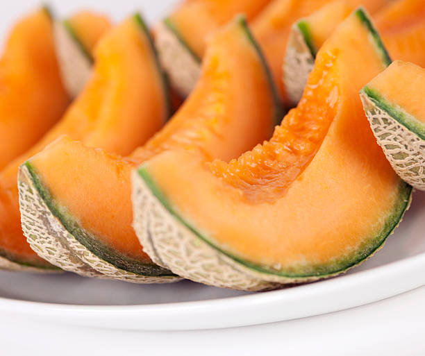 Sliced cantaloupe melons on a plate stock photo