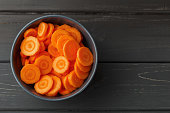 Sliced carrots in a bowl on black wooden background. Top view