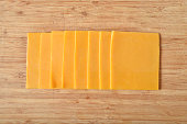 Overhead view of cheddar cheese slices on a cutting board