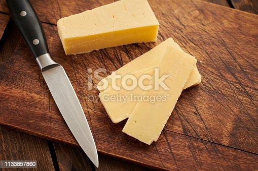 Sliced cheddar cheese on an aged wood chopping board.