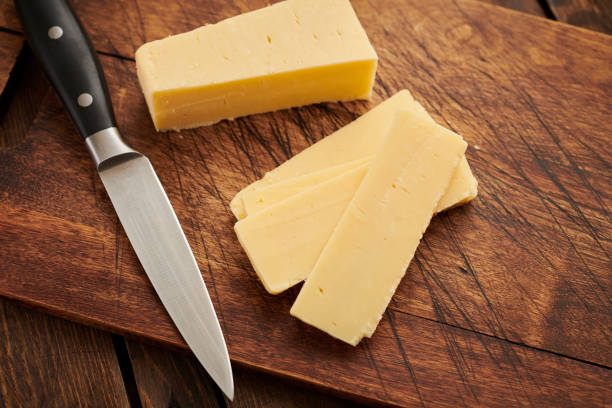 Sliced cheddar cheese on an aged wood chopping board. Sliced cheddar cheese on an aged wood chopping board. cheddar cheese stock pictures, royalty-free photos & images