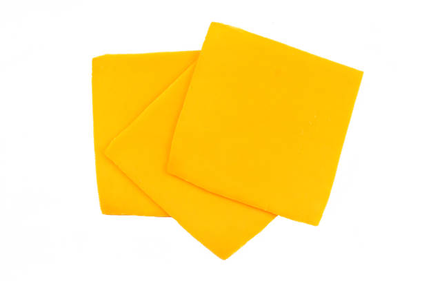 sliced cheddar cheese fromage cheddar en tranches sur un fond blanc cheddar cheese stock pictures, royalty-free photos & images