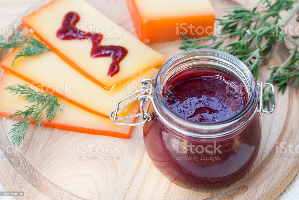Sliced cheese and cherry sauce stock photo