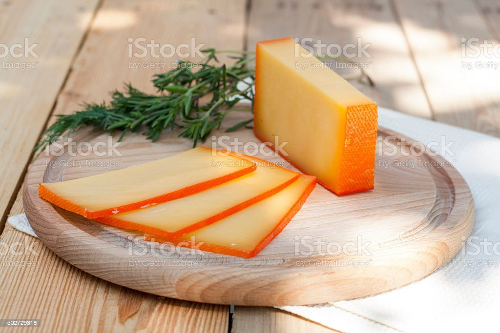 Sliced cheese on wooden board with dill and rosemary royalty-free stock photo