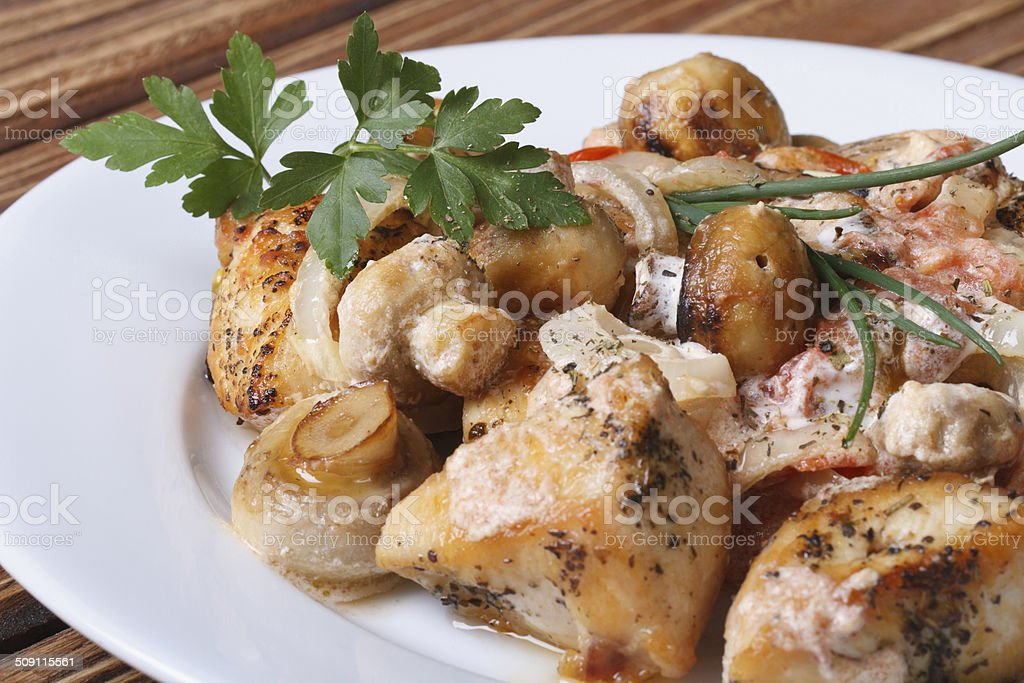 Sliced chicken with mushrooms and sauce on a white plate stock photo