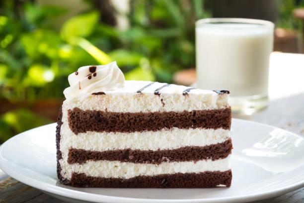 schokoladenkuchen mit schokoladenfondant auf weißen teller über tisch aus holz geschnitten. mit milch serviert. verzieren sie schicht-kuchen mit schlagsahne. - schokoladen biskuitkuchen stock-fotos und bilder